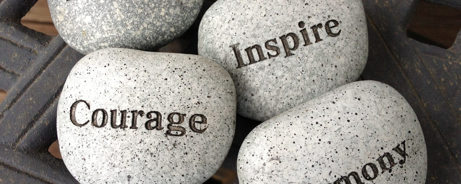 inscribed rocks saying dream courage inspire harmony on top of lattice