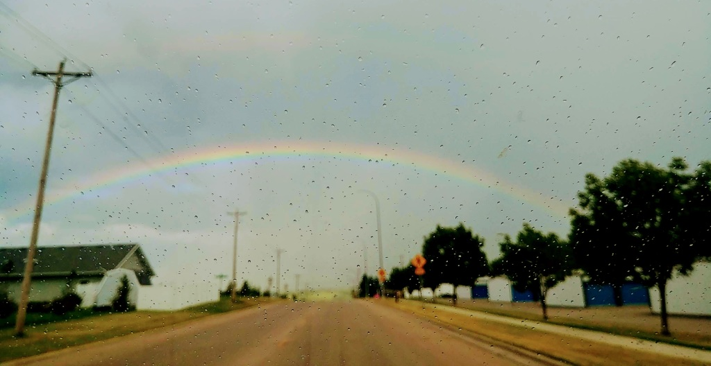 Rainbow over a tree lined road in a small town with raindrops