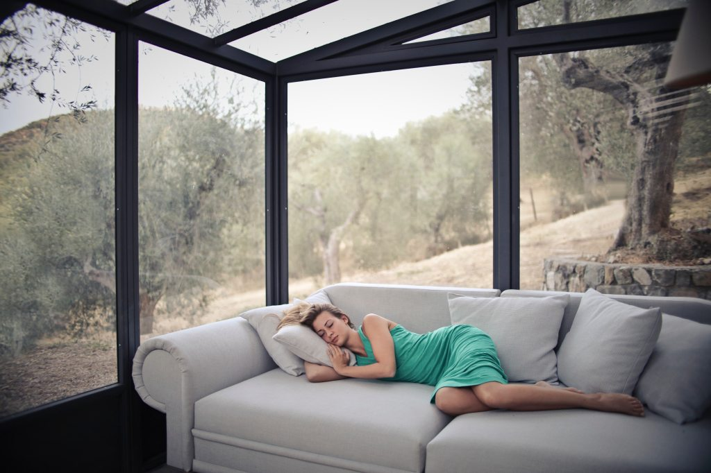 woman sleeping on couch in cabin with glass windows
