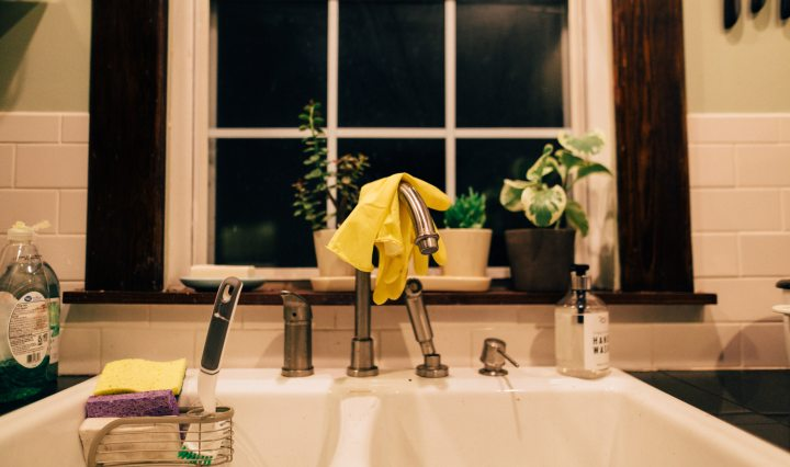 Kitchen sink in front of window with yellow gloves and sponges
