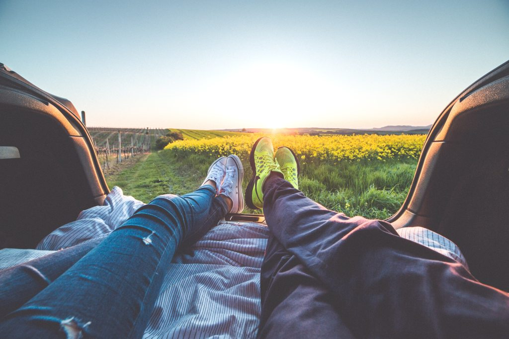 couples feet bed of pickup over fields at sunset