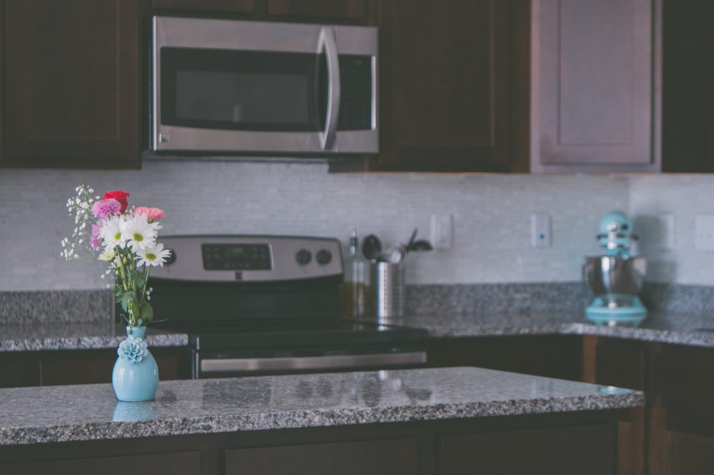 Vase with flowers on granite counter in kitchen
