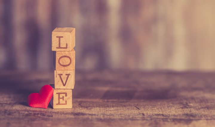 Love spelled out with letter blocks on wood floor with heart