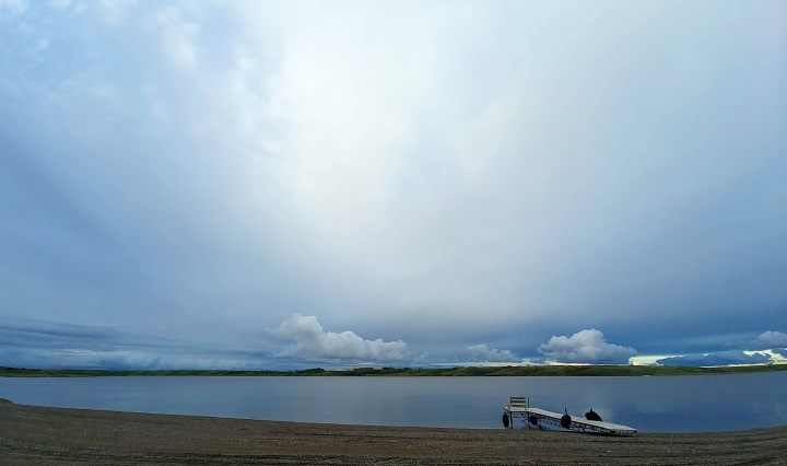 sandy beach and boat dock with rolling hills and clouds across the lake