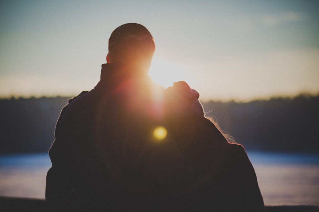 Young couple overlooking sunset on lake