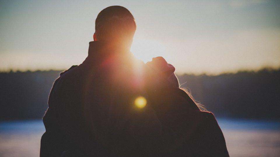 Young couple overlooking sunset on lake