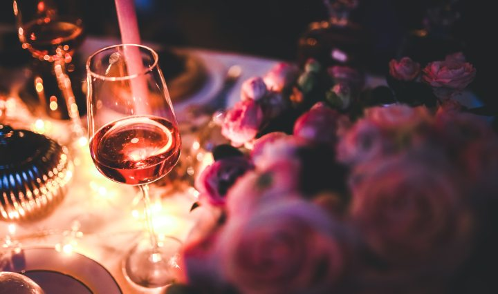 Glass of rose wine next to roses