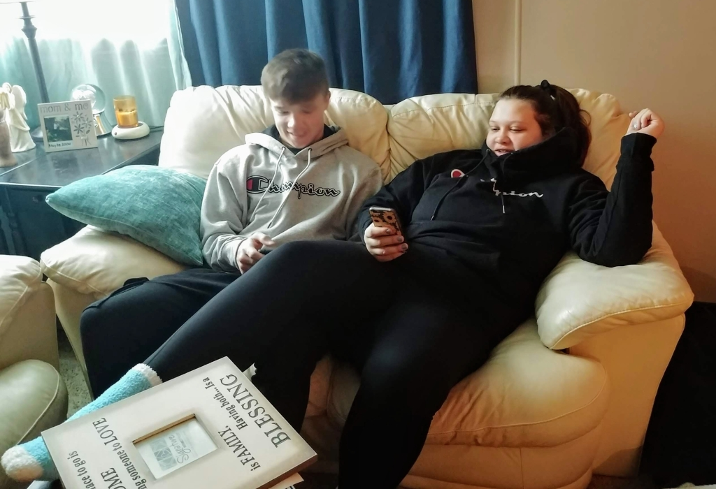 brother and sister on couch playing on their phones