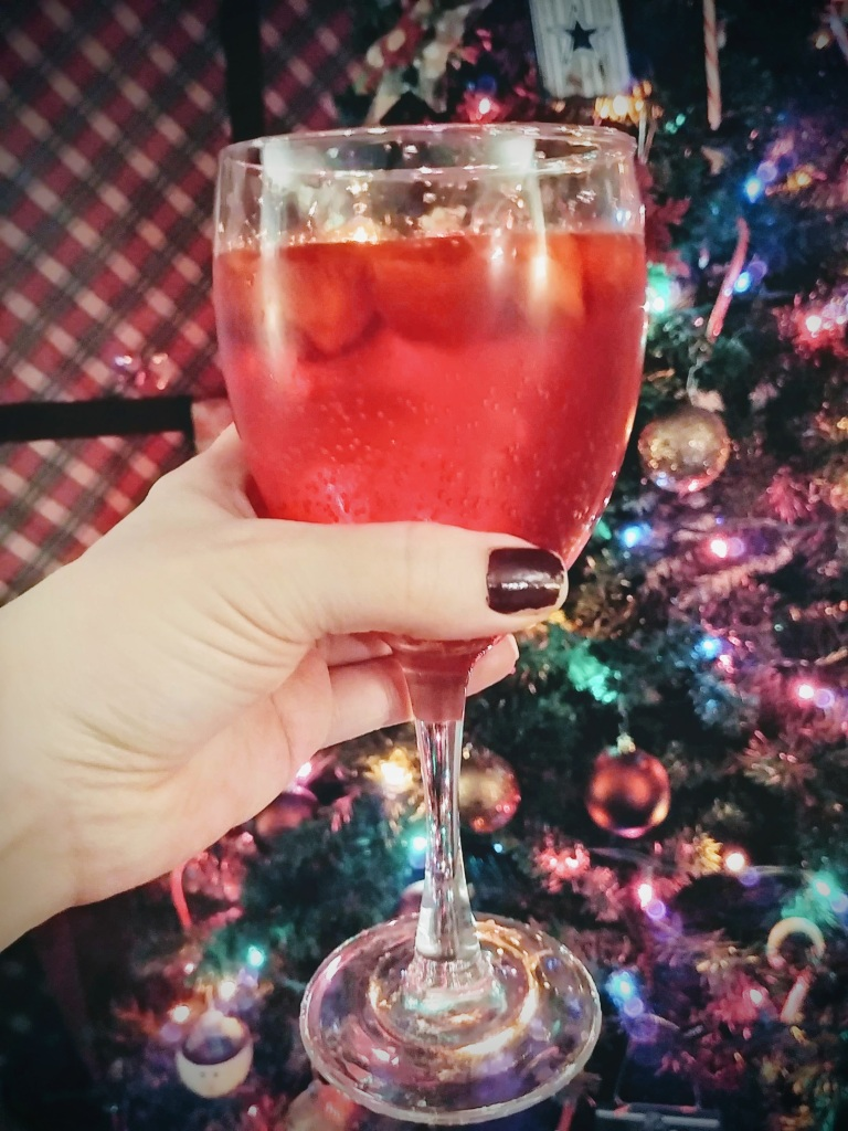 Strawberry mocktail in wine glass in front of tree
