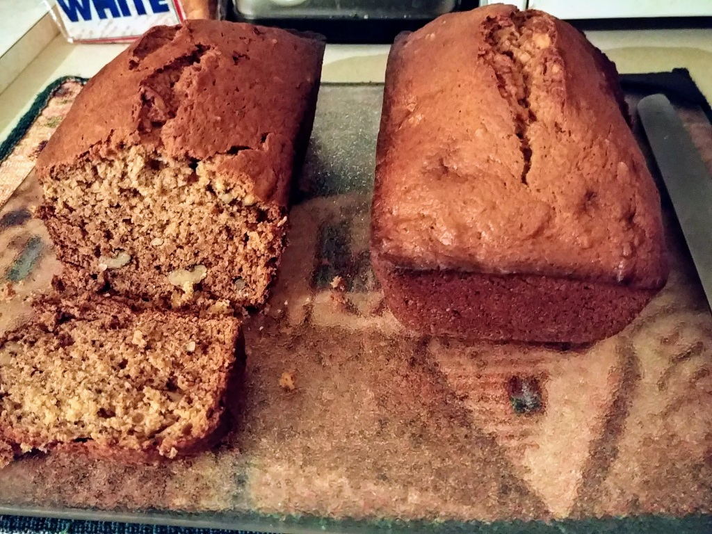 Two loaves of Banana Nut Bread on glass cutting board