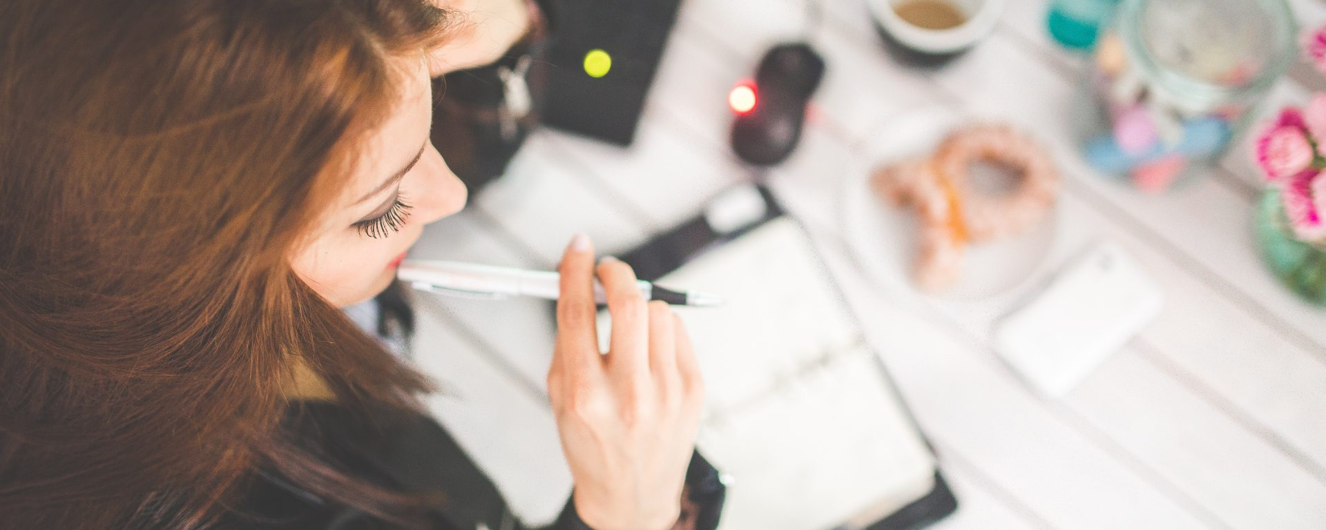 Young woman at desk with pen in mouth