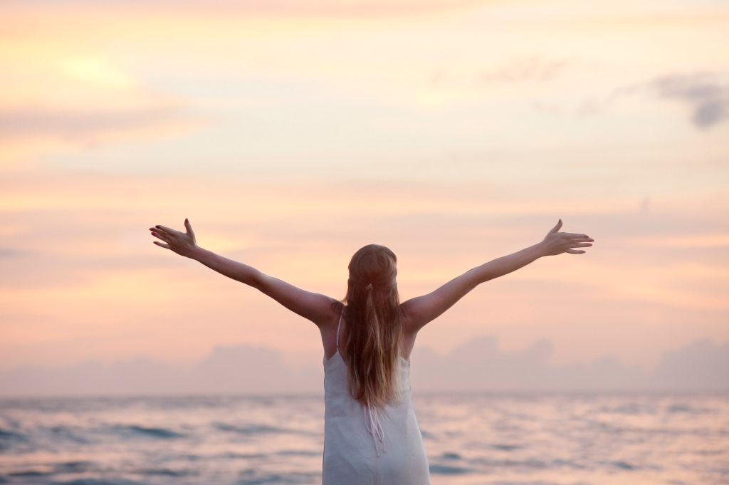 woman-with-arms-raised-at-beach-during-sunset