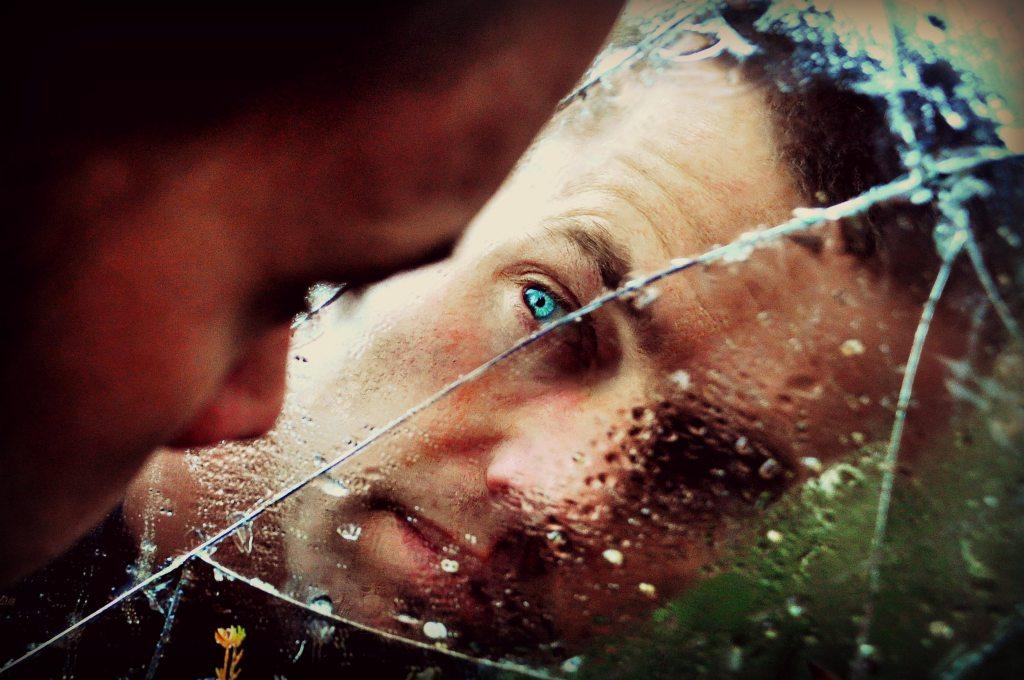 Man Looking in Broken Mirror