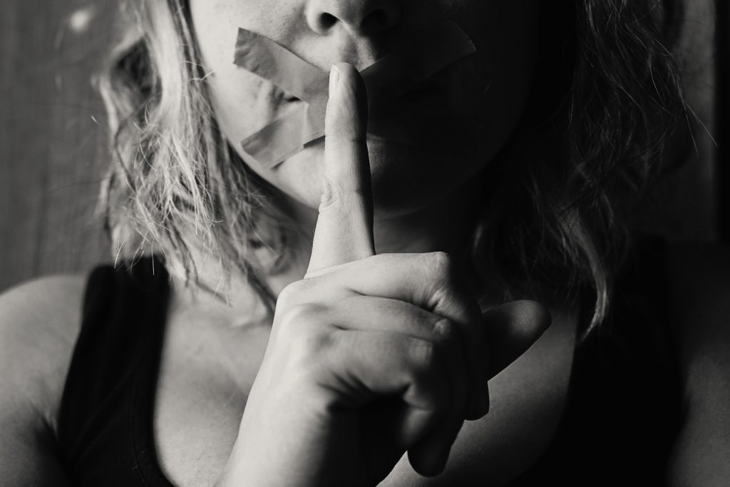 Woman with finger over her lips