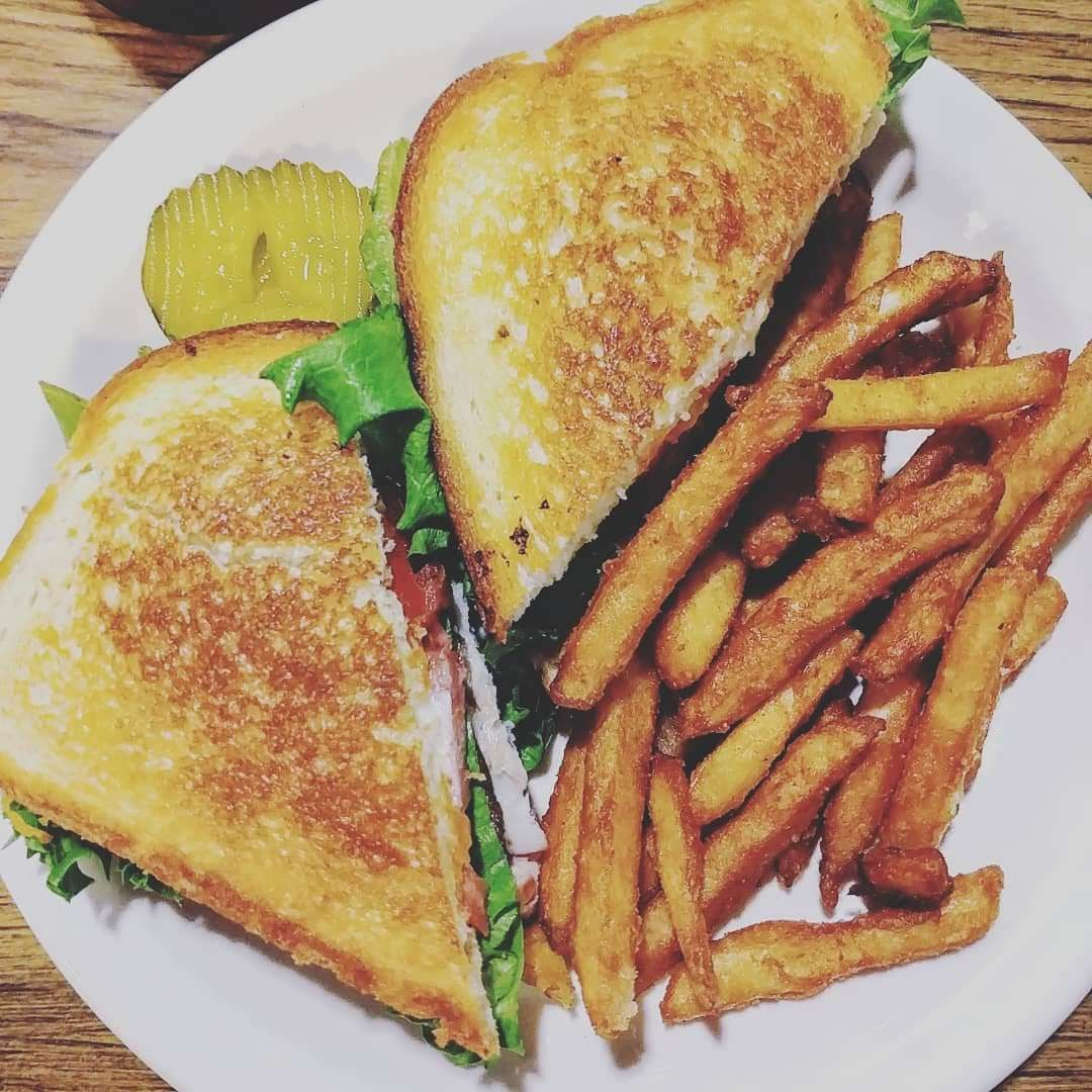 Turkey BLT with fries on white plate