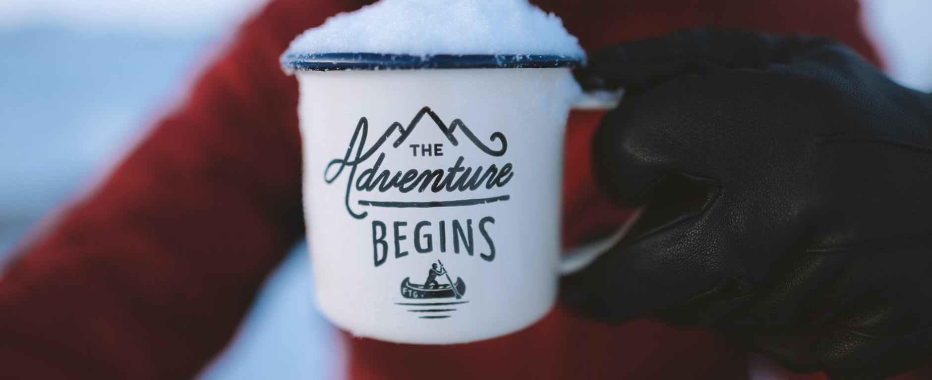 person holding the adventure begins mug