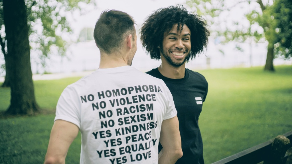 Two Men wearing kindness peace equality and love shirts