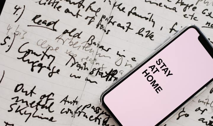 Paper with scribbles and phone on top says Stay at Home