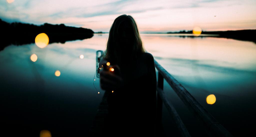 Girl against rails in front of lake with twinkle lights
