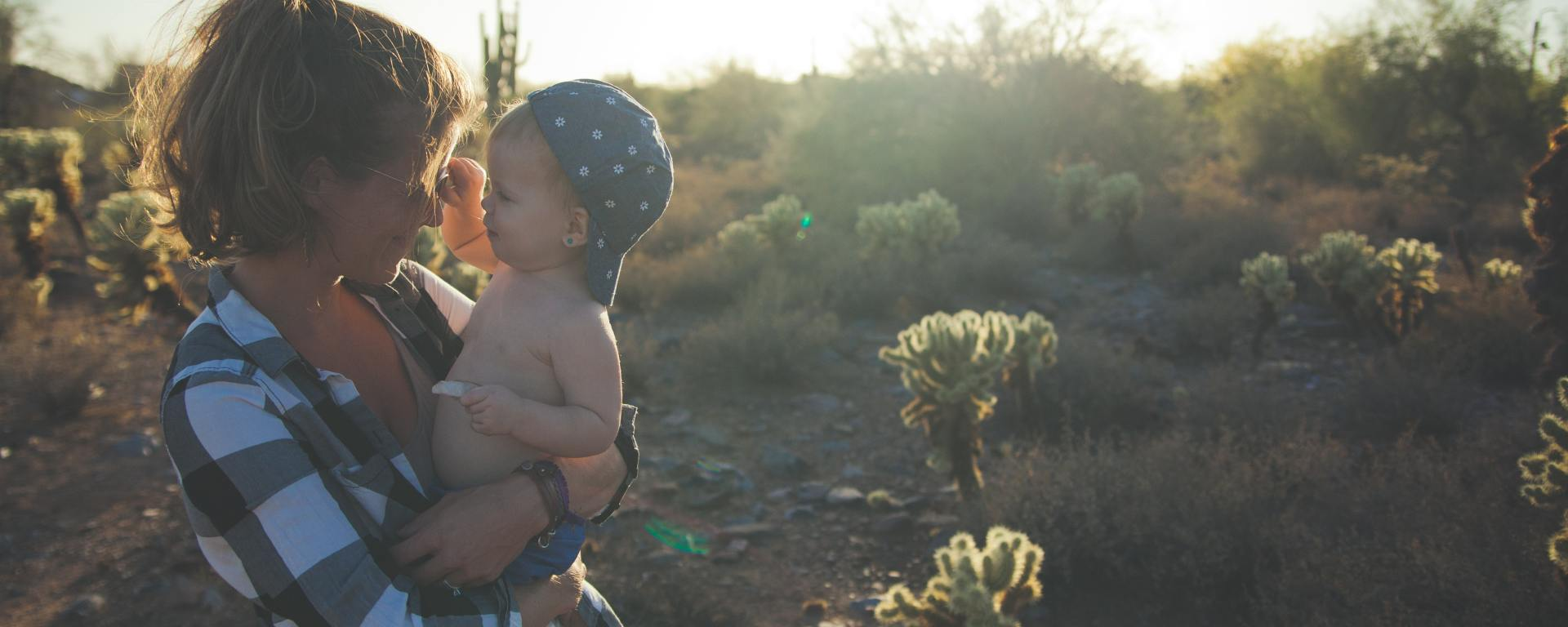 Mom holding little boy on wooded trail